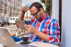 Man with tablet pc in cafe. He is drinking coffee. Stock Photos