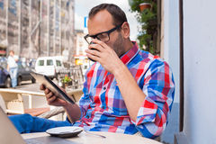 Man with tablet pc in cafe. He is drinking coffee. Royalty Free Stock Photo