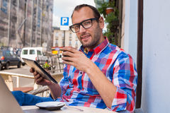 Man with tablet pc in cafe. He is drinking coffee. Man with tablet pc in cafe. He is drinking coffee Royalty Free Stock Photo
