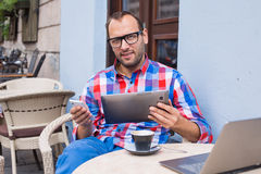 Man with tablet pc in cafe. He is drinking coffee. Stock Photo