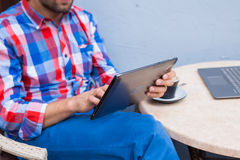Man with tablet pc and coffee in cafe. Royalty Free Stock Image