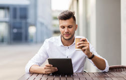 Man with tablet pc and coffee at city cafe Royalty Free Stock Photography