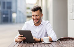 Man with tablet pc and coffee at city cafe Royalty Free Stock Image