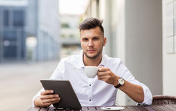 Man with tablet pc and coffee at city cafe Royalty Free Stock Images