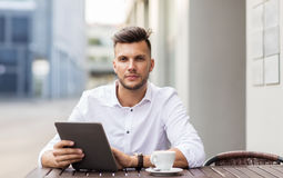 Man with tablet pc and coffee at city cafe Stock Images