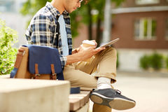 Man with tablet pc and coffee on city street bench Stock Photography