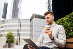 Man with tablet pc and coffee on city street bench Stock Photos