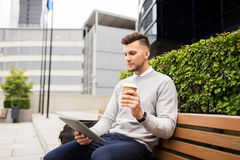 Man with tablet pc and coffee on city street bench Stock Image