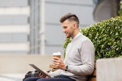 Man with tablet pc and coffee on city street bench Royalty Free Stock Photography