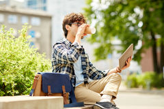Man with tablet pc and coffee on city street bench Royalty Free Stock Images