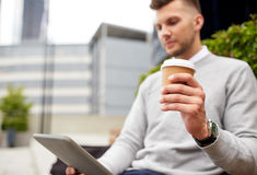 Man with tablet pc and coffee cup on city street Stock Image