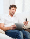 Man with tablet pc and credit card at home Royalty Free Stock Photography