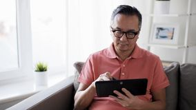 Man with tablet pc and credit card on sofa at home stock video