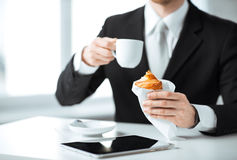 Man with tablet pc and cup of coffee. Businessman with tablet pc, cup of coffee and croissant Stock Image