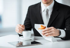 Man with tablet pc and cup of coffee. Man with tablet pc, cup of coffee and croissant Stock Image
