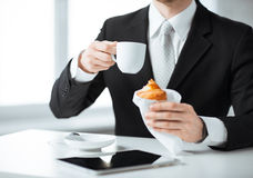 Man with tablet pc and cup of coffee. Businessman with tablet pc, cup of coffee and croissant Stock Photo