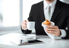 Man with tablet pc and cup of coffee. Businessman with tablet pc, cup of coffee and croissant Royalty Free Stock Photos