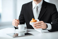 Man with tablet pc and cup of coffee. Man with tablet pc, cup of coffee and croissant Stock Photography