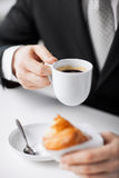 Man with tablet pc and cup of coffee. Man with tablet pc, cup of coffee and croissant Stock Photos