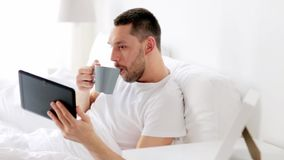 Man with tablet pc drinking coffee in bed at home stock video