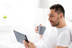 Man with tablet pc drinking coffee in bed at home Stock Photography