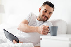 Man with tablet pc drinking coffee in bed at home Royalty Free Stock Photography