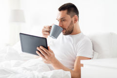 Man with tablet pc drinking coffee in bed at home Stock Photo
