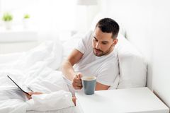Man with tablet pc drinking coffee in bed at home Royalty Free Stock Image