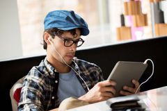 Man with tablet pc and earphones sitting at cafe Royalty Free Stock Photos