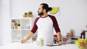 Man with tablet pc eating breakfast at home stock video footage