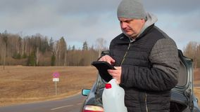 Man with tablet PC and empty can waiting for help near car stock video footage