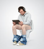 Man with tablet pc and headphones sitting on the toilet Stock Photo