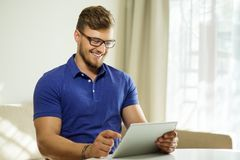 Man with tablet pc at home Stock Images