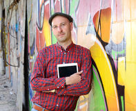 Man with tablet PC is leaning against a graffiti- wall Royalty Free Stock Photos