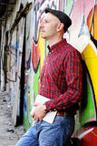 Man with tablet PC is leaning against a graffiti- wall Royalty Free Stock Photo
