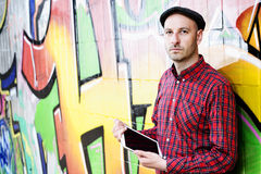 Man with tablet PC is leaning against a graffiti- wall Stock Images