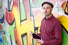 Man with tablet PC is leaning against a graffiti- wall Royalty Free Stock Photography