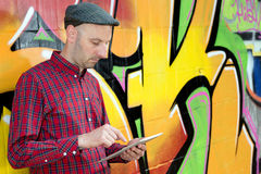 Man with tablet PC is leaning against a graffiti- wall Stock Photography