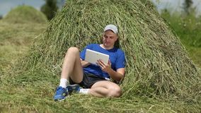 Man with tablet PC lies on a haystack stock video footage