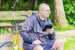 Man with tablet PC near bicycle in the park Royalty Free Stock Photography