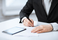 Man with tablet pc signing paper Royalty Free Stock Photography