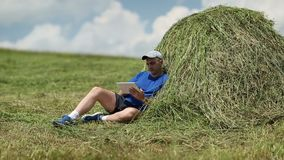 Man with tablet PC sits near haystack stock footage
