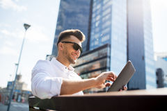 Man with tablet pc sitting on city street bench Royalty Free Stock Photos