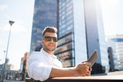 Man with tablet pc sitting on city street bench Royalty Free Stock Images