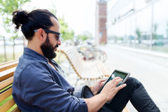 Man with tablet pc sitting on city street bench Stock Photo