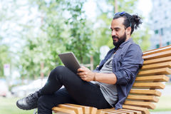 Man with tablet pc sitting on city street bench Royalty Free Stock Image