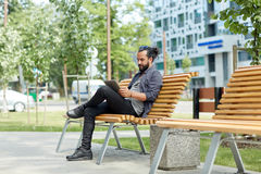 Man with tablet pc sitting on city street bench Stock Images