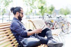 Man with tablet pc sitting on city street bench Royalty Free Stock Photo