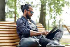 Man with tablet pc sitting on city street bench Stock Photography