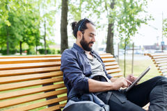 Man with tablet pc sitting on city street bench Royalty Free Stock Photography